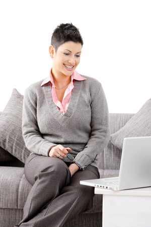 Happy young woman sitting on sofa at home and working on laptop computer, smiling. Isolated on white background. photo