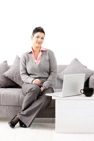 Happy young woman sitting on sofa at home and working on laptop computer, smiling. Isolated on white background. Stock Photo - 7016315