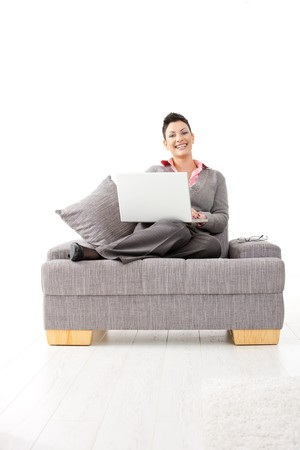 gratified: Happy young woman sitting on couch working on laptop computer at home, smiling.