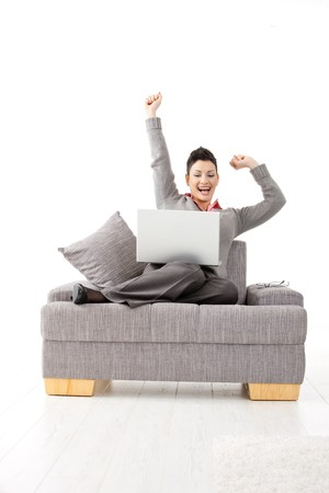 Happy businesswoman sitting on sofa with laptop computer. Celebrating business succes with hands raised, smiling. photo