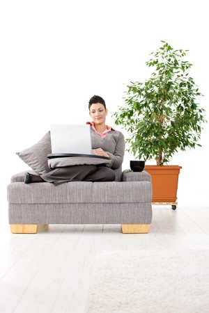 Young woman sitting on couch working on laptop computer at home, smiling. White background with green plant. photo