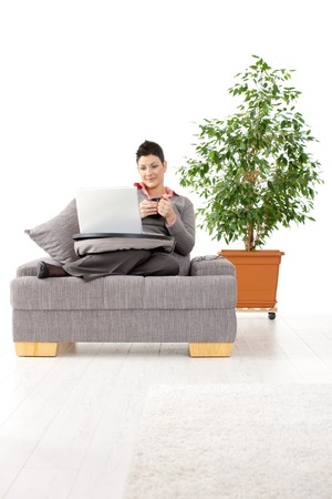 Young woman sitting on couch teleworking on laptop computer at home. Stock Photo - 7016282