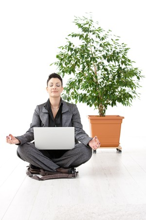 Young businesswoman sitting in yoga lotus position, holding laptop computer, meditating with closed eyes. photo