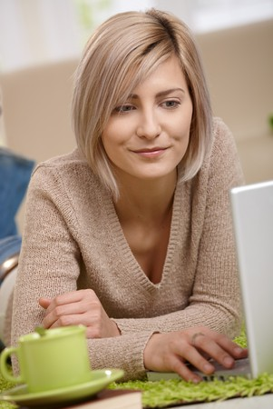 telework: Portrait of attractive young blonde woman lying on floor at home looking at laptop, smiling. Stock Photo