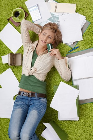 image size: Happy woman lying on floor holding credit card, bills all around.