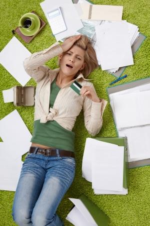 cuenta: Conmocionado mujer acostado en el piso de la sala de estar rodeado de facturas, la celebraci�n de la tarjeta de cr�dito, con la mano en la frente en alto �ngulo de vista. Foto de archivo