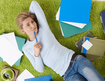 above head: Smiling woman surrounded with documents lying on living room floor, daydreaming with hand under head. Stock Photo