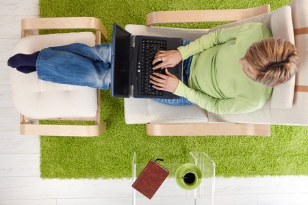 elevated view: Woman typing on laptop keyboard sitting in armchair with legs crossed on footboard in high angle view.