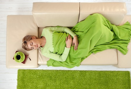 lay down: Sleeping woman in high angle view lying on sofa under blanket.