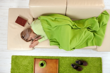 ハイアングルビュー: ハイアングルの毛布の下のソファに横たわっているで眠っている女性。