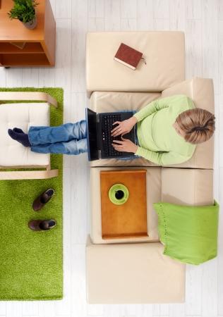 ハイアングルビュー: 女性ハイアングルのソファーに座っているコンピューターのキーボードで入力します。 写真素材