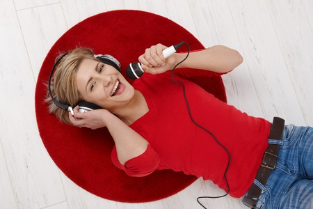 red jeans: Woman lying on round red carpet of living room floor with headphones holding microphone, singing in high angle view. Stock Photo