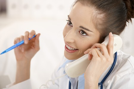 Portrait of young female doctor sitting at desk in doctors room calling, looking away, smiling. photo
