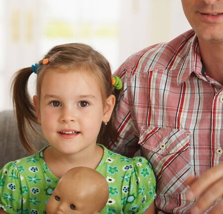Portrait of happy little daughter sitting beside father, looking at camera, smiling.  Stock Photo - 7058828