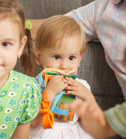 Babygirl sitting on sofa at home with family around her and playing. Stock Photo - 7058771