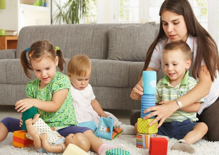 Mother and 3 happy children sitting on floor at home playing together with toy blocks smiling. Stock Photo - 7058900