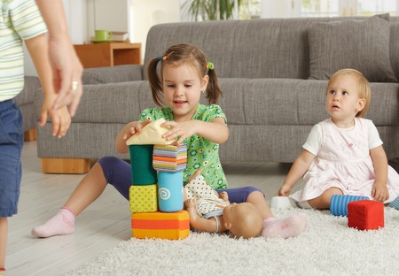 the three sisters: Kids playing with toy blocks sitting on floor in front of sofa at home Stock Photo