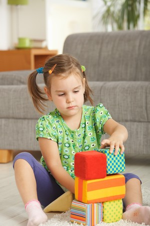 Concentrating little girl (3-4 years) playing with toy blocks at home. Stock Photo - 7058826