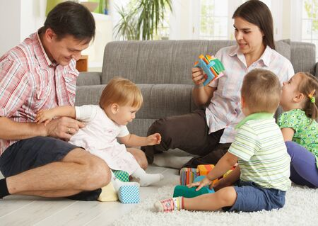 Happy nuclear family with 3 children playing together at home, smiling. Stock Photo - 7058898