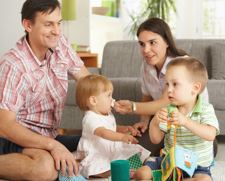 Happy nuclear family with 2 children playing together at home, smiling. photo