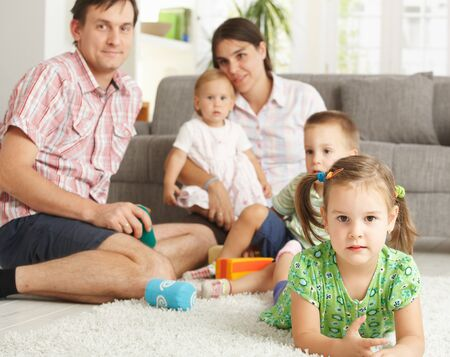 prone: Little girl (3-4 years) lying on floor at home with nuclear family in background. Stock Photo