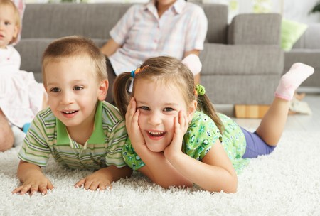 3 4 length: Happy children having fun posing on floor of in living room at home.