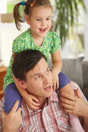 Happy little girl sitting on father's shoulders having fun at home Stock Photo - 7058875
