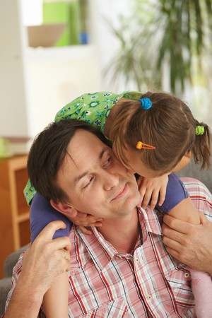 girl bonding: Little girl sitting on fathers shoulders kissig his face.