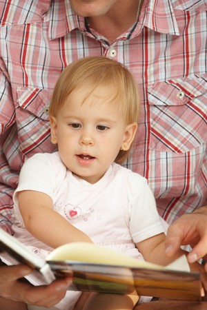 Cute baby girl (1-2 years toddler age) looking at book handheld by father. Stock Photo - 7058825