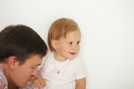 Affectionate father kissing cute baby girl, white background, smiling. Copy space on right. photo