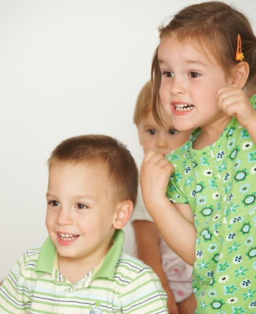 Happy little children at attention, white background. Copy space in top left corner. Stock fotó