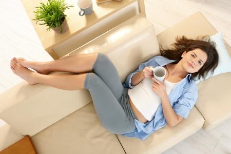 pies bonitos: Chica descansando sobre el sof� con pies, sonriente, sosteniendo la taza de caf�, en la vista a�rea.