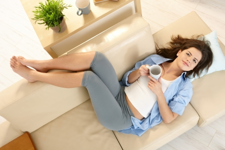 Girl resting on couch with feet up, smiling, holding coffee cup, in overhead view. photo