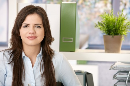 Portrait of pretty young woman sitting in office. photo