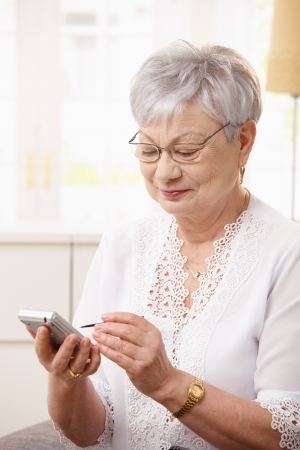 Elderly lady using smartphone at home. photo