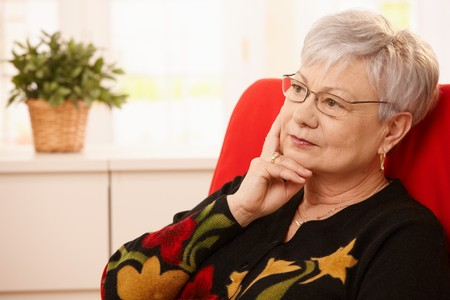 Senior woman sitting in armchair, daydreaming, looking away. Stock Photo - 7058948