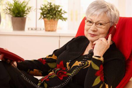 Senior lady using landline phone, sitting in living room armchair, looking at camera. Stock Photo - 7058958