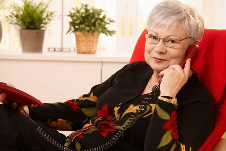 Senior lady using landline phone, sitting in living room armchair, looking at camera. photo