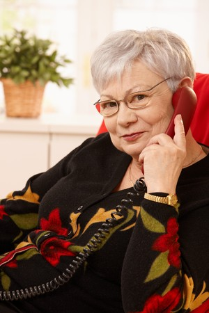 mujeres sentadas: Retrato de mujer senior en llamada de tel�fono fijo en casa, mirando a c�mara, sonriendo.
