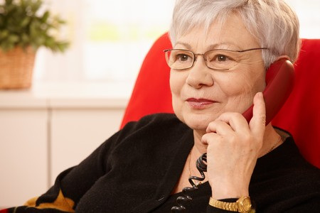 american seniors: Closeup portrait of senior lady on landline phone call, smiling.