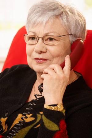 Closeup portrait of senior woman with phone in hand, wearing glasses, smiling. photo