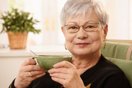 tea cosy: Closeup portrait of mature lady sitting at home holding teacup, looking at camera.