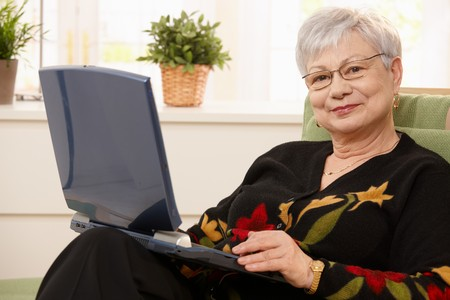 boomers: Smiling elderly lady holding laptop computer, sitting in armchair, smiling at camera.