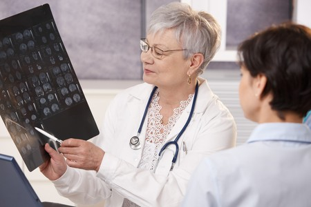 Doctor and patient discussing x-ray results in doctors office. Stock Photo