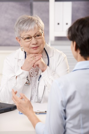 active listening: Senior doctor listening to patient in office, smiling. Stock Photo