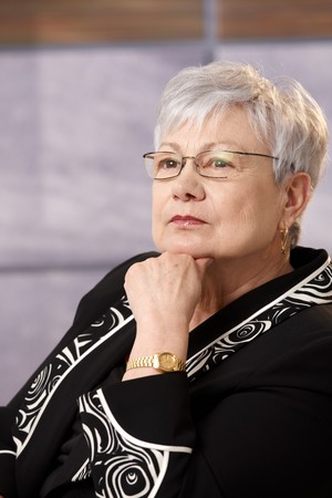 Portrait of active senior businesswoman in thought, concentrating. photo