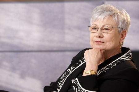 1 senior: Retrato de mujer senior activa en ropa inteligente, pensando.  Foto de archivo