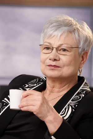 Portrait of nice senior woman wearing glasses having coffee. Stock Photo - 7059003