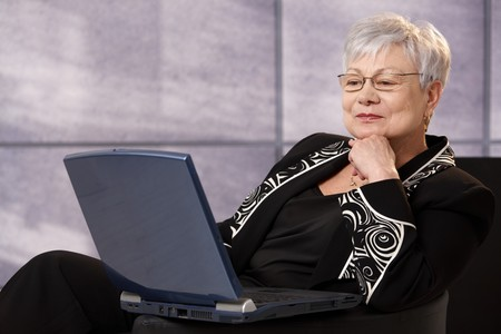 Senior businesswoman sitting in office armchair, using laptop computer, smiling. Stock Photo - 7058935