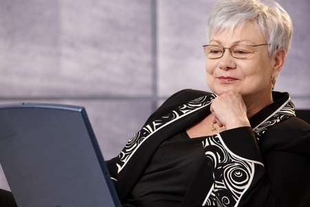 ropa casual: Senior empresaria mirando la pantalla del ordenador port�til, sonriendo.